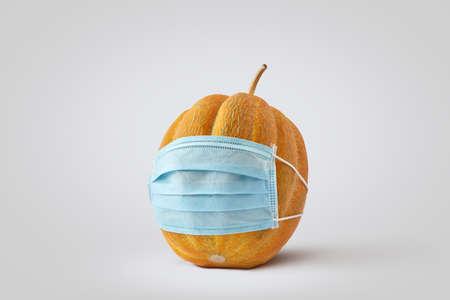 Fresh pumpkin in a medical protective face mask. Standard-Bild