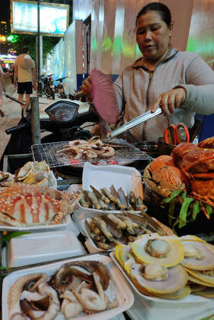 Vietnamese street food in trays for sale. Fried lobster, crab, mussels, oysters for tourists. Exotic dishes cooked on the outdoor grill. Publikacyjne