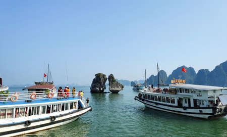 Picturesque view of UNESCO Ha Long bay. Tourist boats are swimming near chicken rocks.
