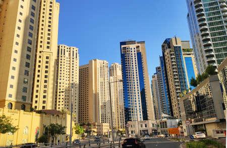Modern skyscrapers are shining in sunrise, street is shown in Dubai Marina.