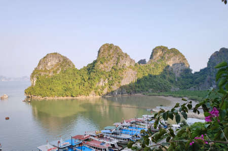 Picturesque view of UNESCO Ha Long bay. Tourist boats are moored to the shore.