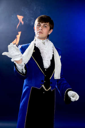 Portrait of prestidigitator with fire on arm.