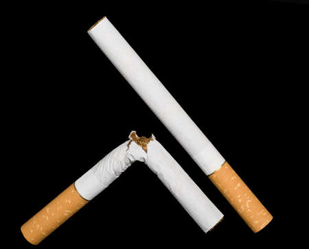 deleterious: Two cigarettes isolated on black background.