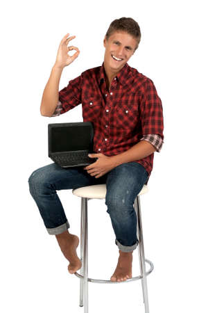 Successful young man is working on laptop. Isolated on white background. Stock Photo