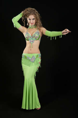 Beautiful  dancer in eastern costume on black background. Stock Photo - 8179756