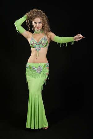Beautiful  dancer in eastern costume on black background. photo