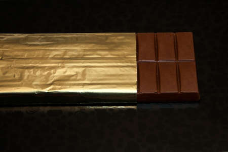 Milk chocolate on black abstract background photo