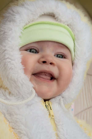 neonate: Smiling baby in a winter fur coat Stock Photo