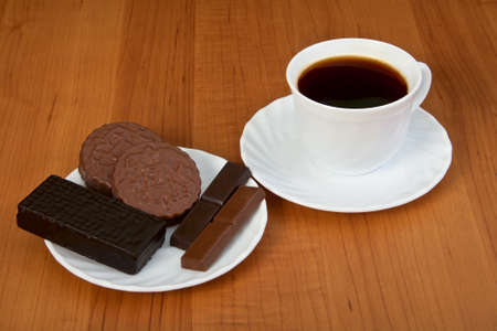 Cup of coffee and chocolate candy on wooden table. photo
