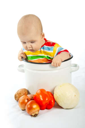 Baby sitting in the big white kitchen saucepan with vegetables. photo