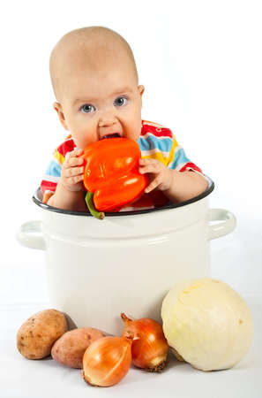 Baby sitting in the big white kitchen saucepan with vegetables. Stock Photo - 12187993