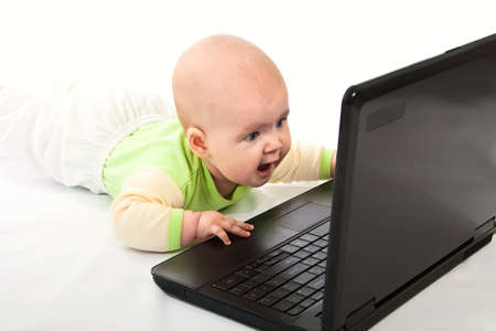 Portrait of little baby with laptop on white background photo