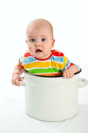 Baby sitting in the big white kitchen saucepan.  photo