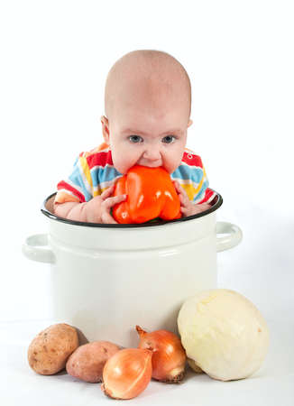 Baby sitting in the big white kitchen saucepan with vegetables.