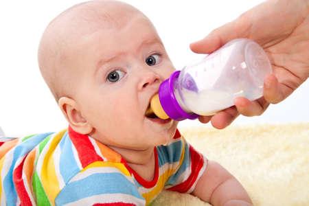 Little baby is feeding milk from bottle photo