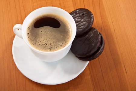 Cup of coffee and chocolate cookies on wooden table. photo