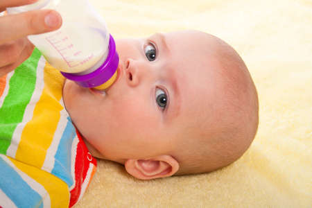 Little baby is feeding milk from bottle photo
