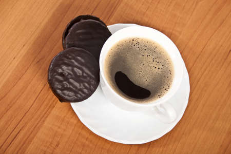 Cup of coffee and chocolate cookies on wooden table photo