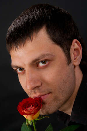 Portrait of handsome man with rose on dark background. photo