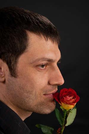 Portrait of handsome man with rose on dark background  photo