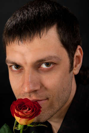 Portrait of handsome man with rose on dark background  photo