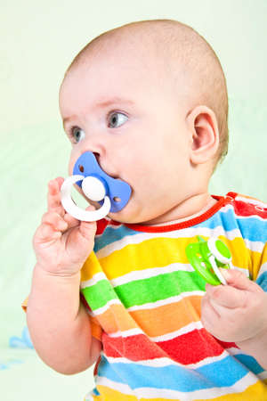 Baby girl with pacifier on light background Stock Photo