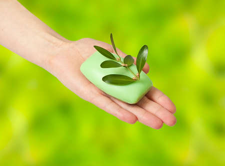 Woman hand with soap and spring on abstract background photo