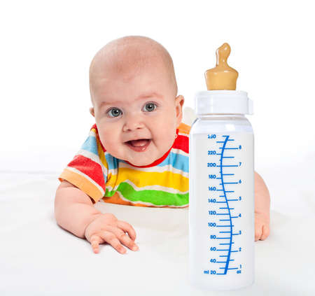 Little baby is crawling to babys bottle with milk