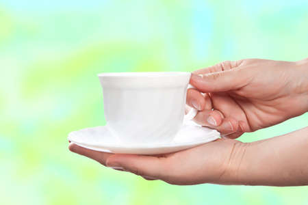 White cup with saucer in woman hands on abstract background. photo