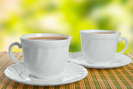 Two teacups on straw napkin and abstract fire background.