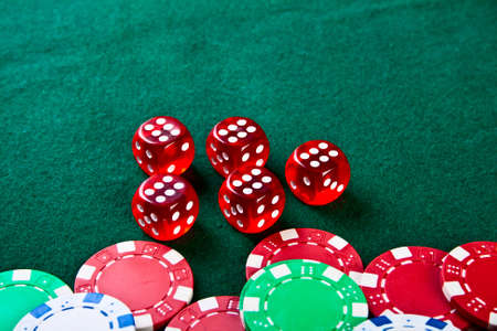 Group of chips and dices on the green cloth photo