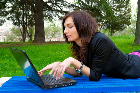 Young woman is working on laptop on a park bench photo