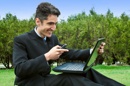 Young man with cell phones and laptop in the park  Stock Photo - 13270094
