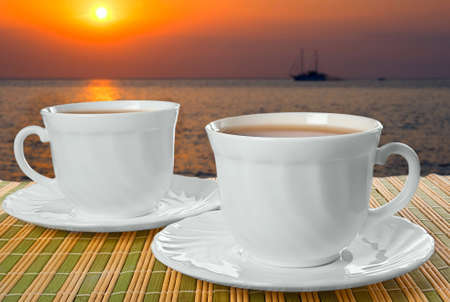 Two white cups with saucer on straw napkin and background of sunset. photo