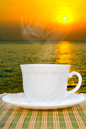 White cup with saucer on straw napkin and background of sunset. photo