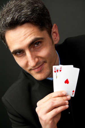 Young lucky gambler with cards in hand  photo