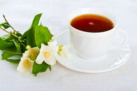 Teacup with saucer and jasmine flower on the white napkin  photo