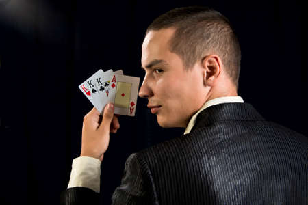 gambler: Young lucky gambler with cards in hand.