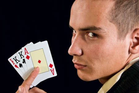Young lucky gambler with cards in hand.