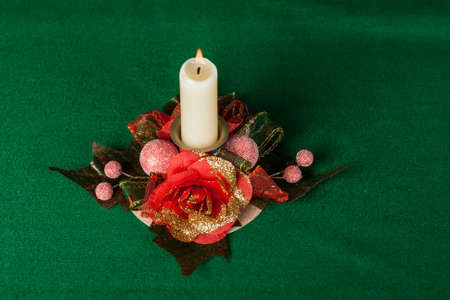 candle with floral decoration on green background photo