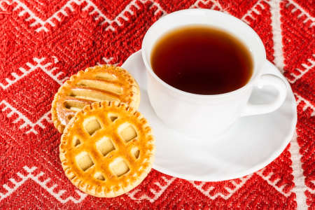 freshly baked biscuits with cheese and teacup on red tablecloth photo