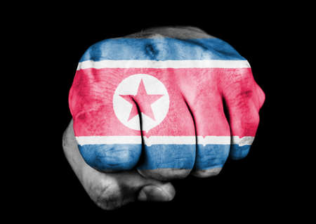 fist with the flag of the North Korea on black background Stock Photo