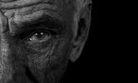 Monochrome portrait of an elderly man on black background Stock Photo