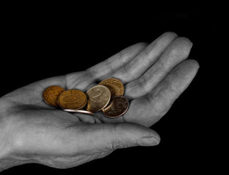 priceless: Hand with coins isolated on black