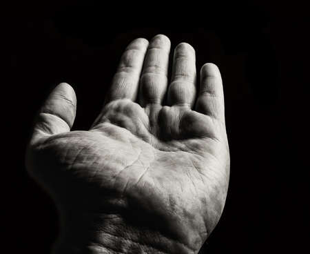Man's hand on a black background. Monochrome image. Stock Photo - 27545216