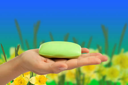Green soap bar in hand on flowers abstract background.
