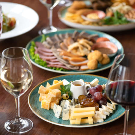 Cheese and wine are the perfect snack. Mix of cheeses and glasses of wine. Delicious Snacks or appetizer food background, served dishes in restaurant.