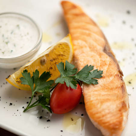 Red fish, salmon or trout baked or fried with vegetables. Slice of cooked Sea fish fillet with tomato, lemon, parsley and sauce on plate. Close up, Soft focus.