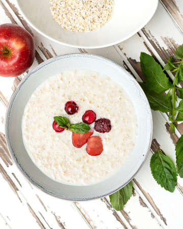 Oatmeal with milk and berries. Nutritious breakfast, wholesome healthy food. Bowl of porridge cereal oats with fresh red berries and mint on on white wooden rustic table. High angle view.