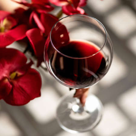 Glass of red wine and red orchid flowers on wooden table with sun glare. Alcoholic drink. Close up shot, soft focus.